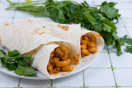 Buritto - traditional Mexican food, on a plate on a blue tablecloth Imagens