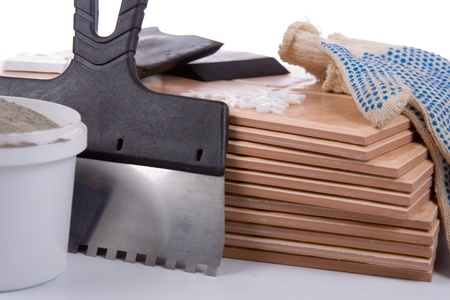 Ceramic tiles and trowel for repairs  isolated on a white background