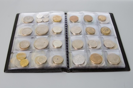 Open the album with a collection of coins on a gray background Stock Photo