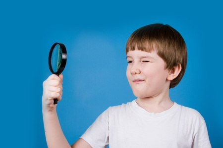 schoolkid search: Boy with magnifying glass on a blue background Stock Photo
