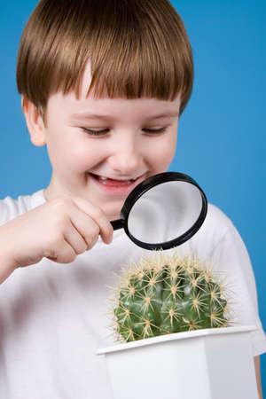 schoolkid search: Muchacho sonriente que mira a trav�s de una lupa en un cactus sobre un fondo azul