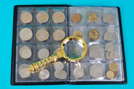 numismatics: Magnifying glass and  album with a collection of coins on a blue background close up Stock Photo