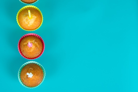 Festive cupcakes with a candles on gradient background,top view photo
