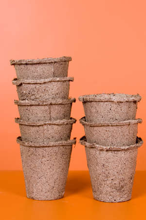 Peat pots on a brown background photo