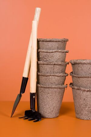 Peat pots and garden tools on a brown background photo