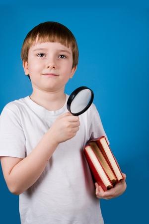 schoolkid search: Ni�o con glassa aumento y la pila de libros sobre un fondo azul