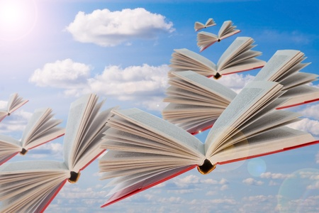 Books are flying  against the background of the cloudy sky