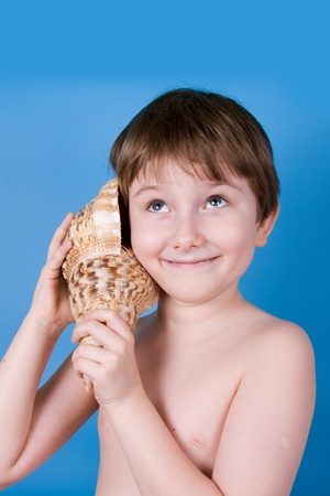 Boy listens to shell on a blue background