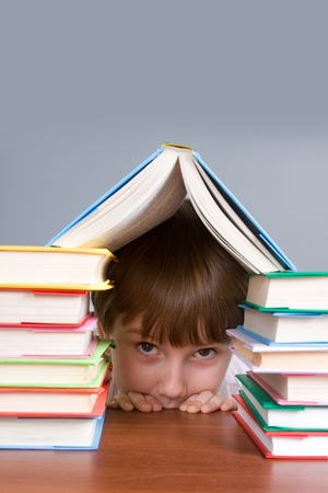 Boy hid behind the books on a gray background photo