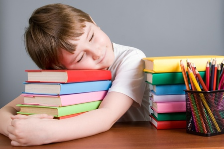 Tired boy sleeps on the books on a gray background photo