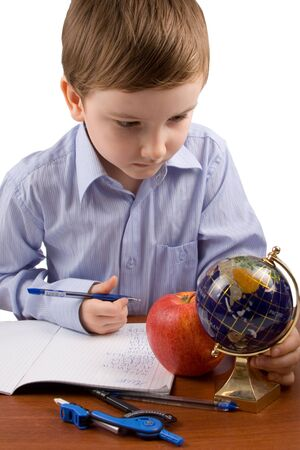 Serious boy writes in a notebook on a table, isolated on a white background photo