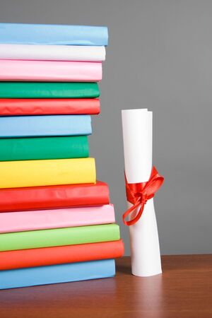 Diploma and stack of books on a gray background photo