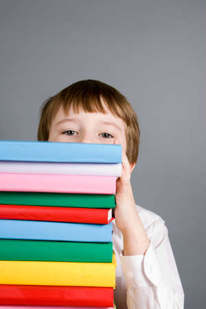 Boy looks out from a stack of books on a gray background photo