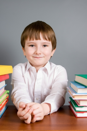 Boy with books on a gray background photo