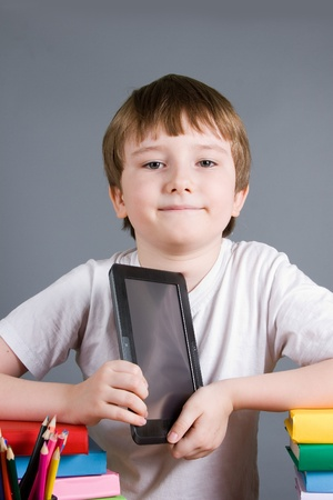 Boy with e-book is sitting at the table on a gray background Stock Photo