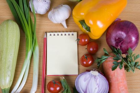 Fresh vegetables and a notebook on a wooden table Stock Photo - 13866910