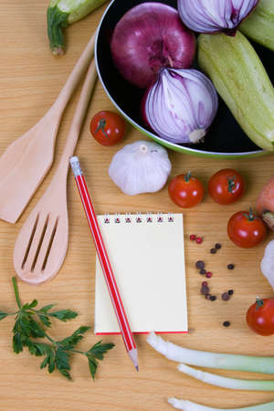 Fresh vegetables and a notebook on a wooden table Stock Photo - 13866912