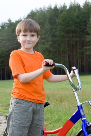 Boy with the bike on the nature of the spring