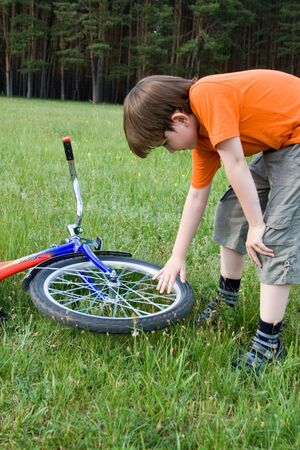 Doy looks at the broken wheel of the bike in a meadow photo