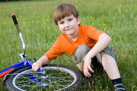 Boy sits in a meadow next to the bike photo