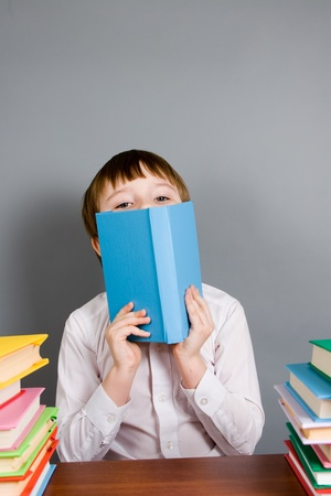 Boy reads a book on a gray background photo