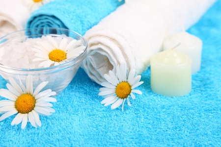 Spa still life with blue towels, flowers, salt and towels photo