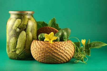Pickled cucumbers with leaves and flowers on a green background Stock Photo - 14677944