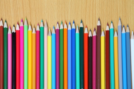 Colored pencils on a wooden table. Close-up. photo