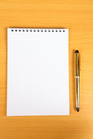 White blank notebook with yellow pen on  a wooden table photo