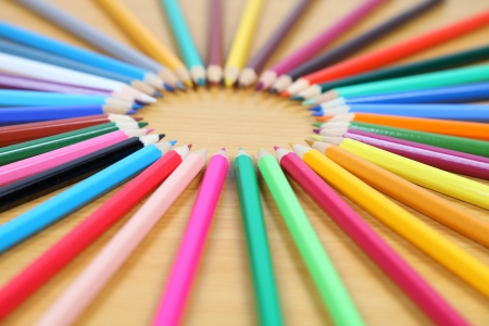 Pencils lie on a circle on a wooden table. Close-up. photo