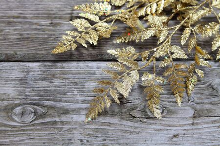 Christmas decorations: golden twig on a wooden background photo