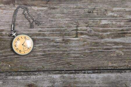 Vintage pocket watch on chain on wooden background  photo