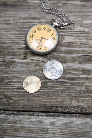 Old clock and U.S. coins on a wooden background photo