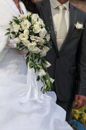 Bridal bouquet of white roses and lisianthus in hands of newlywed  Stock Photo
