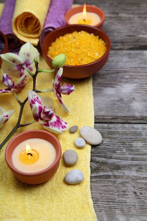 Spa concept: soap, salt for baths, a flower and towels on a wooden background photo