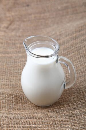 microelements: Glass jug with milk on a brown fabric background