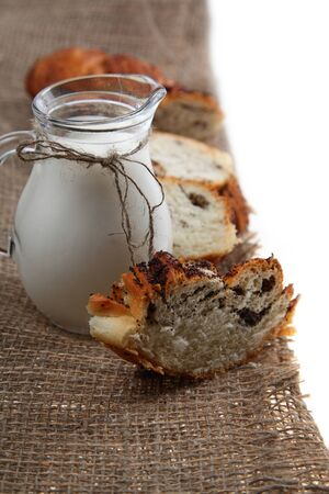 microelements: Glass jug with milk and bread on a brown fabric on a white background