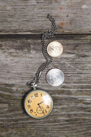 Old clock and U.S. coins on a wooden background Stock Photo - 16920630