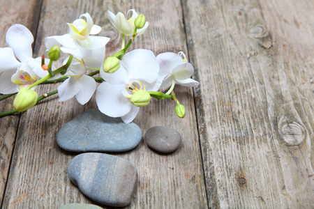 Aromatherapy spa set. Zen stones and orchid on wooden background