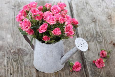 bouquet fleurs: Bouquet de roses dans un arrosoir sur un fond de bois