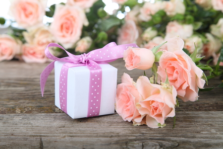 Bouquet of pink roses and gift on a wooden background photo