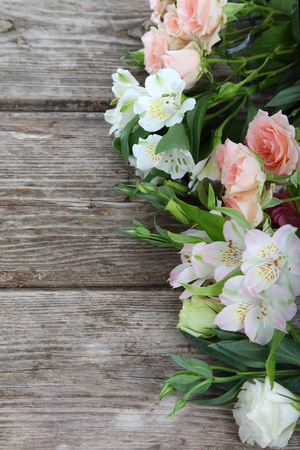 Bouquet of pink and white flowers on a wooden background photo