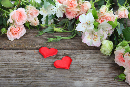 Bouquet of of beautiful flowers and red hearts on a wooden background photo