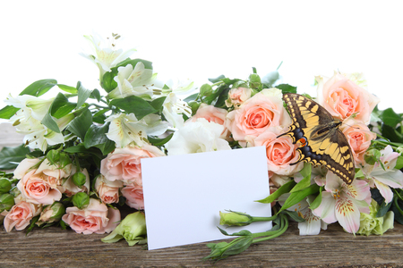 Bouquet of beautiful flowers, butterfly and greeting card on a wooden table photo