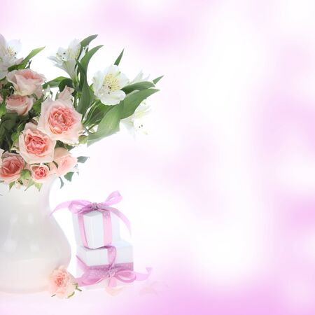 Bouquet of flowers  in a vase and gifts on an abstract background photo