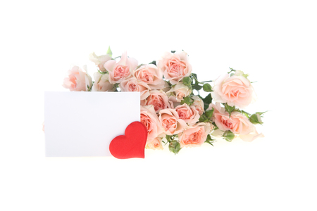 Bouquet of pink roses with greeting card and heart on a white background photo