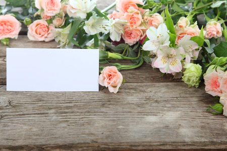 Bouquet of beautiful flowers and greeting card on a wooden background photo