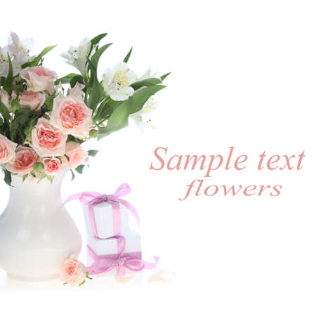 Bouquet of flowers  in a vase and gifts on a white background photo