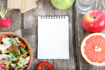 Healthy food for diet and blank note on a wooden table