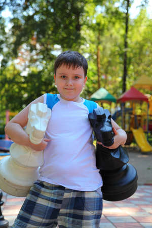 rival rivals rivalry season: Boy plays in the big chess in a summer park